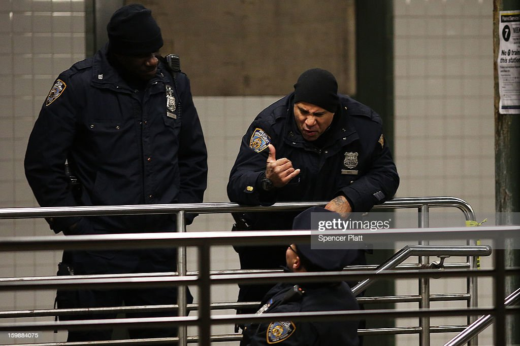 Police stand guard near where the body of an apparent suicide victim waits to be removed at a subway station in Times Square on January 22, 2013 in New York City. New York City has been experiencing a rash of high-profile incidents involving individuals being hit by trains in suicides, accidents and people being pushed to their deaths.