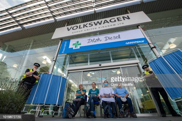 Police stand guard next to Greenpeace activists who have chained themselves to entrances at Volkswagen United Kingdom Headquarters as they campaign...