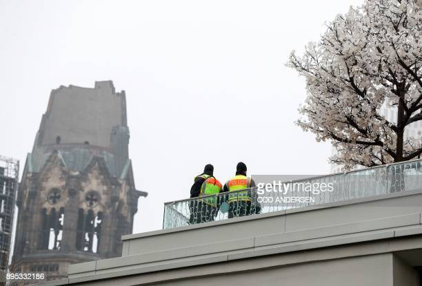 Police stand guard on a balcony near the KaiserWilhelmGedaechtniskirche prior to commemorating ceremonies for the victims of last year's deadly truck...
