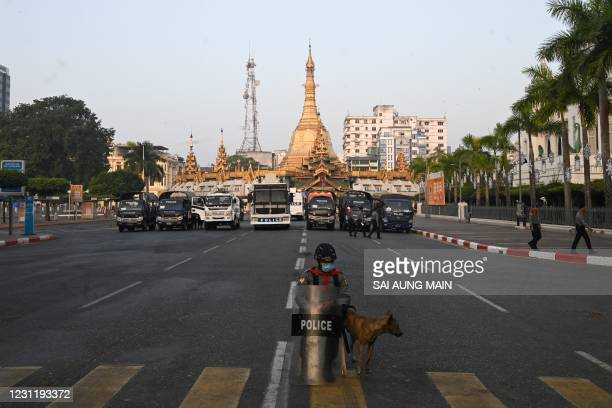 Police stand guard on a barricaded road outside the Yangon City Hall and Sule Pagoda in Yangon on February 16, 2021.