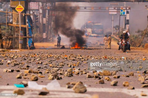 Police stand guard on a road afte protesters set fire on buses during a demonstration against the Indian government's Citizenship Amendment Bill in...