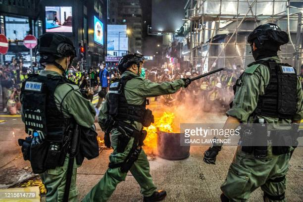 TOPSHOT Police stand guard on a road to deter prodemocracy protesters from blocking roads in the Mong Kok district of Hong Kong on May 27 as the...