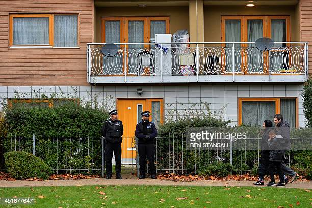 Police stand guard outside a block of residential flats in south London on November 24 2013 where investigations have centred following the arrest of...