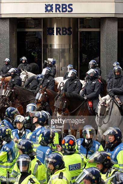 Police stand guard outside a branch of RBS as anticapitalist and climate change activists demonstrate in the City of London on April 1 2009 in London...