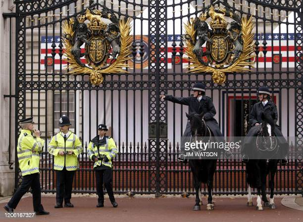 Police stand guard outside the center gate of Buckingham Palace in London 18 November 2003 where a protester climbed up and hung an American flag...