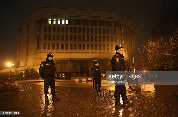 Police stand guard outside the Crimea regional parliament building after parliamentarians voted for a May 25th referendum on Crimea's autonomy...