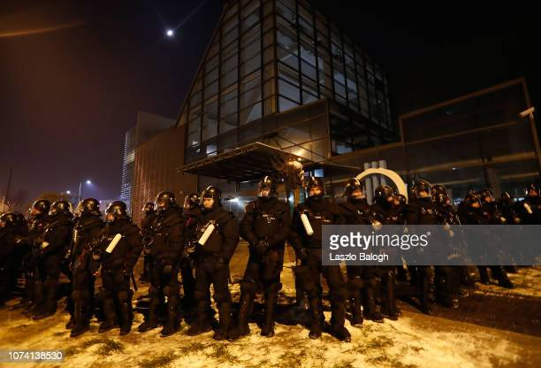 Police stand guard outside the headquaters of Hungarian state television during a demonstrators protesting against recent legislative measures...