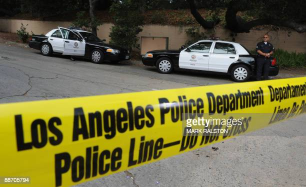 Police stand guard outside the rented Holmby Hills home in Los Angeles on June 26, 2009 where music legend Michael Jackson died after allegedly...