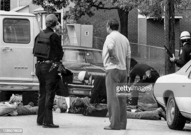 Police stand guard while other officers handcuff KKK members following a shooting between Klan members and anti-Klan demonstrators. The incident left...