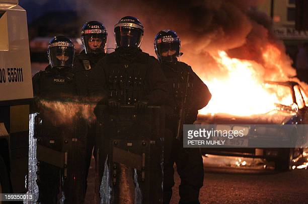 Police stand guard with a baton gun and riot shields in front of a burning car left following violence between loyalists nationalists and the police...