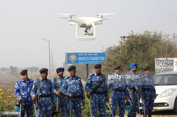 Police stand guard with a hovering drone near a jail where Indian guru and convicted murderer Gurmeet Ram Rahim Singh was being held in anticipation...