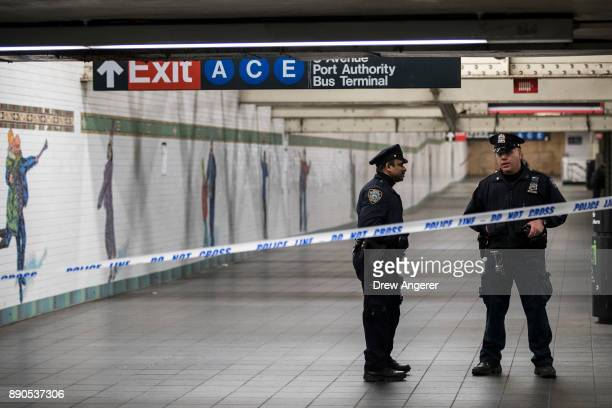 Police stand in a closedoff underground walkway near the site of a pipe bomb explosion in the tunnel that connects the Times Square subway station to...