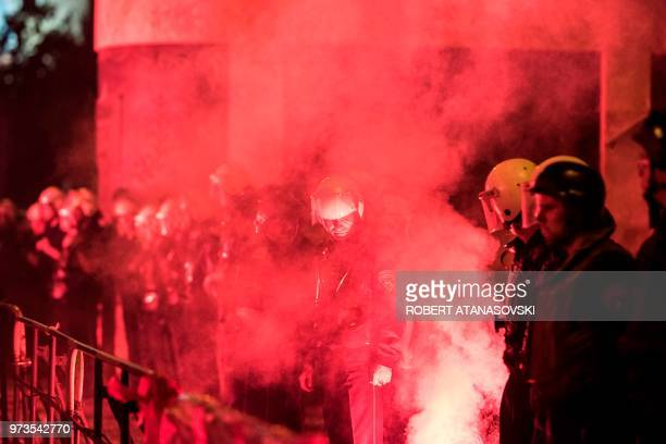 Police stand in a cordon surrounded by the smoke of flares in front of the parliament building in Skopje on June 13 2018 as people protest against...