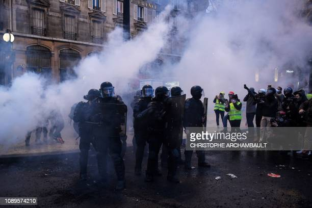 Police stand in a group in tear gas smoke during an antigovernment demonstration called by the yellow vests movement on the Place de la Bastille in...