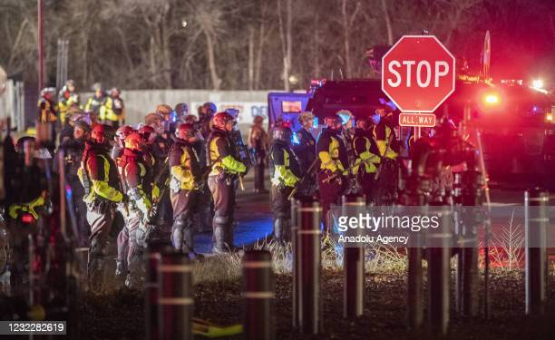 Police stand in a line as they try to clear the area of protestors as protests over police killing of Daunte Wright continue in Brooklyn Center,...