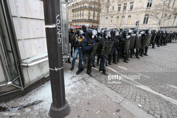 Police stand in front of broken windows near the Arc de Triomphe during an antigovernment demonstration called by the quotYellow Vestquot movement on...