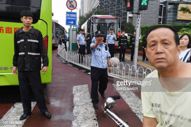 Police stand in front of China's Banking Regulatory Commission as a cyclist looks on in Beijing on August 6 2018 Hundreds of police swarmed the...