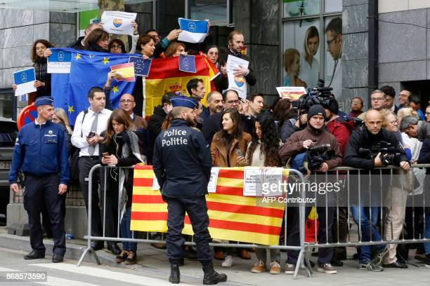 Police stand in front of people holding a Catalan, Spanish and European flags during a demonstration of pro and anti-Catalan independance in front of...