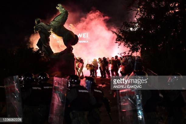 Police stand in tear gas smoke outside the National Assembly building in Belgrade on July 10 during clashes with protesters at a demonstration...