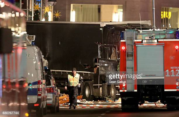 Police stand near a black lorry truck that is likely the one that ploughed through a Christmas market on December 19 2016 in Berlin Germany At least...