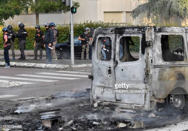 Police stand near a burnt van in the Gresilles area of Dijon, eastern France, on June 15 as new tensions flared in the city after it was rocked by a...