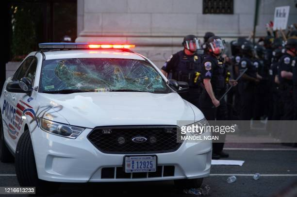 Police stand near a police car damaged by protesters during a protest against the death of George Floyd, near the White House on May 31, 2020 in...