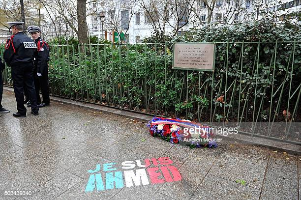 Police stand near the memorial stone in tribute to the police Officer Ahmed Merabet stone in next to former Charlie Hebdo office on January 5 2016 in...