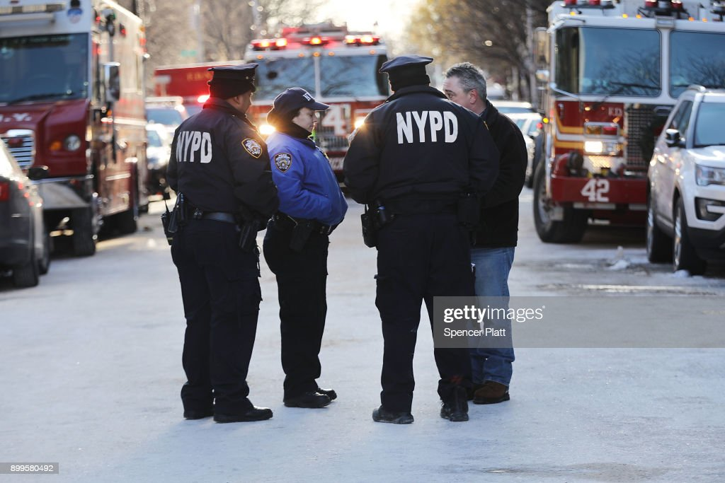 Police stand near the scene of a deadly in the Bronx on December 29, 2017 in New York City. At least 12 people, including at least four children were killed in the early evening blaze which officials believe was started by a child playing with the stove.