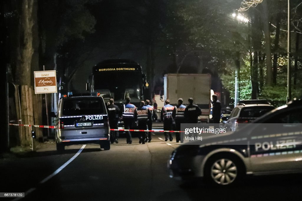 Police stand near the team bus of the Borussia Dortmund football club after the bus was damaged in an explosion on April 11, 2017 in Dortmund, Germany. According to police an explosion detonated as the bus was leaving the hotel where the team was staying to bring them to their Champions League game against Monaco. So far one person, team member Marc Bartra, is reported injured.