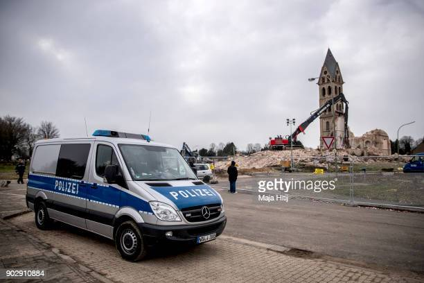 Police stand nearby as an excavator demolishes Saint Lambertus church following protests by activists on January 9 2018 in Immerath Germany The...