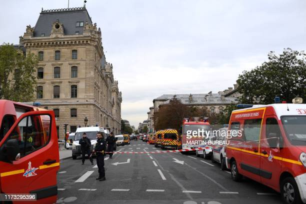Police stand next to firefighter vehicles near Paris prefecture de police on October 3 2019 after four officers were killed in a knife attack A knife...