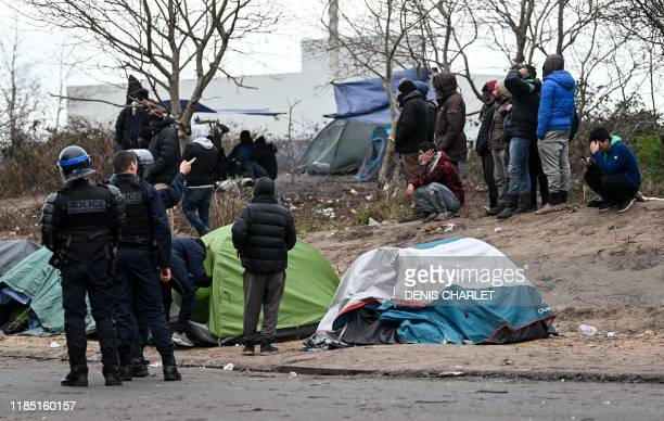 Police stand next to migrants in a makeshift camp in Calais, northern France, on November 28, 2019 following clashes between migrants. - At least...