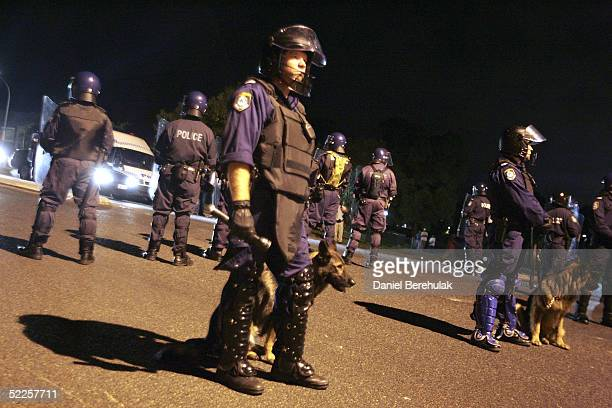 Police stand on guard during the fourth night of sporadic rioting between youths and police in Macquarie Fields on February 28, 2005 in Sydney,...