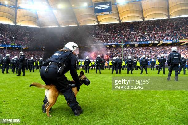Police stand on the pitch after Hamburg supporters throw fireworks ahead the final whistle of the German first division Bundesliga football match...