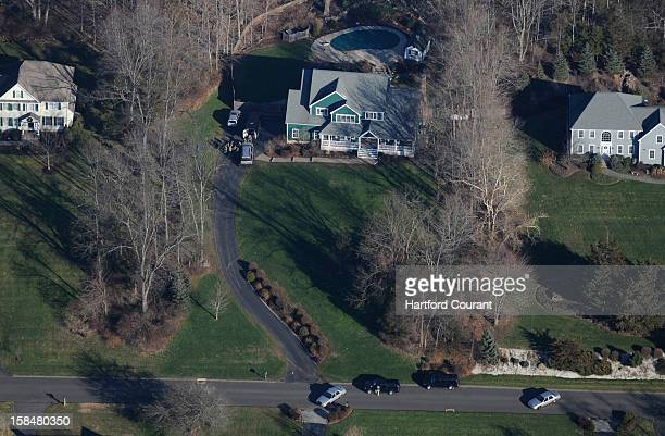 Police stand outside a home center adjacent to the white house on left being investigated by police on Yogananda Street in Newtown Connecticut Friday...