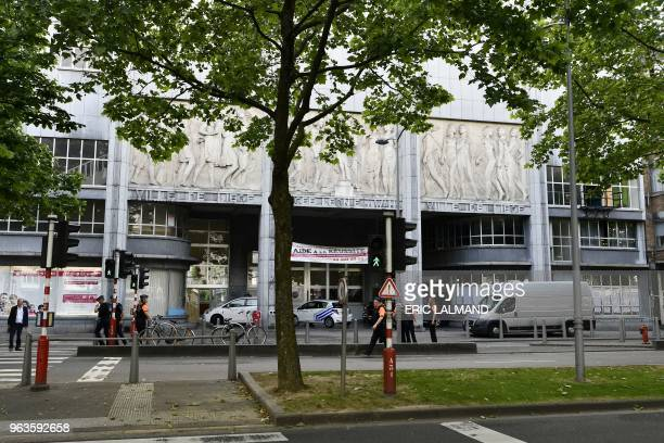 Police stand outside the Athenee Leonie de Waha school where a gunman took a woman hostage during a deadly shooting in the eastern Belgian city of...