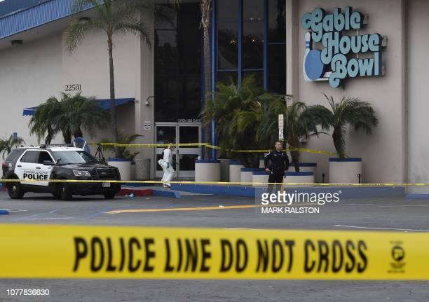 TOPSHOT Police stand outside the Gable House Bowl center after 3 men were killed and 4 injured in a shooting at the bowling alley in Torrance...