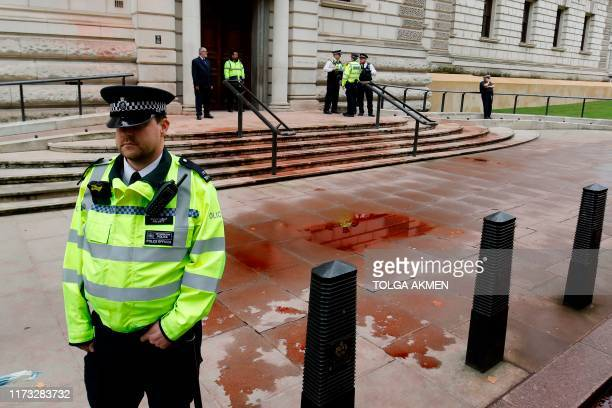 Police stand outside to secure the Treasury building in central London on October 3 2019 after protesters from climate group Extinction Rebellion...
