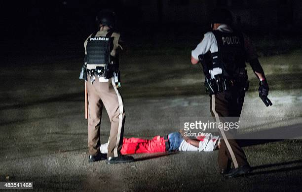 Police stand over a man with gunshot wounds lying in a parking lot after a shoot out with police along West Florissant Street during a demonstration...