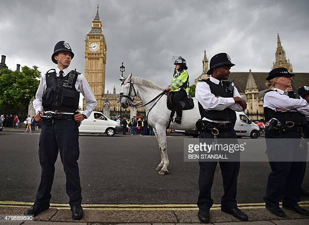 Police stand ready as protesters gather in Parliament Square in central London on July 8 as British finance minister George Osborne unveiled fresh...