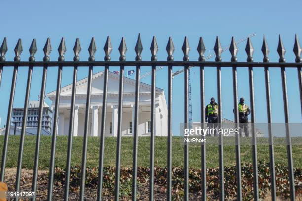 Police stand watch on a hill near the state capitol building during a rally organized by The Virginia Citizens Defense League on Capitol Square near...
