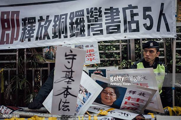 A police standguard as protesters tape placards to barriers during a rally outside of Liaison Office of the Central People's Government in the Hong...