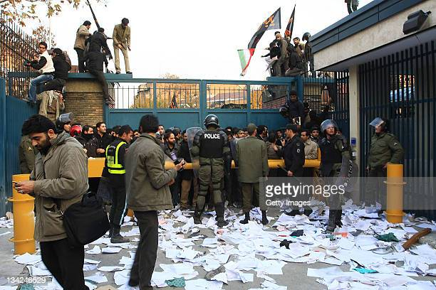 Police standing amidst paper strewn across the floor hold protesters behind a barrier as others climb a security gate following a break in to the...
