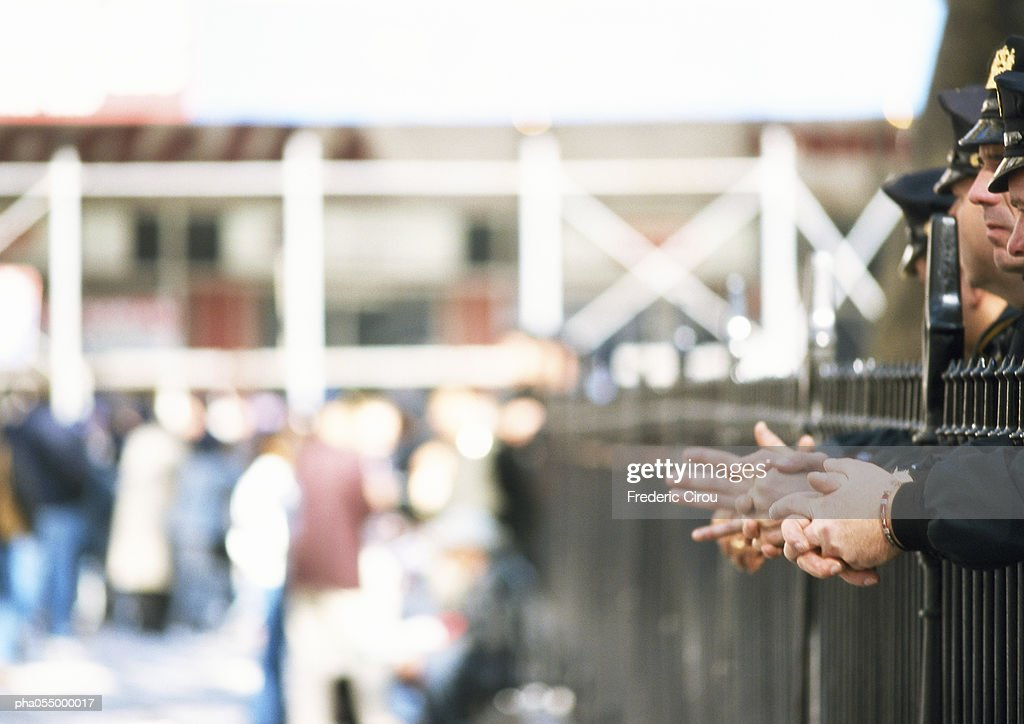 Police standing behind railings, partial side view, crowd in background, blurred : Stockfoto