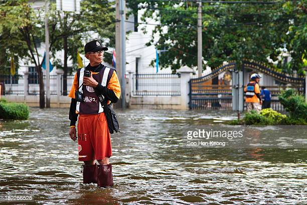 Police standing on flood water directing traffic with a loud speaker outside of Chatuchak Park, Bangkok, Thailand during 2011 flood