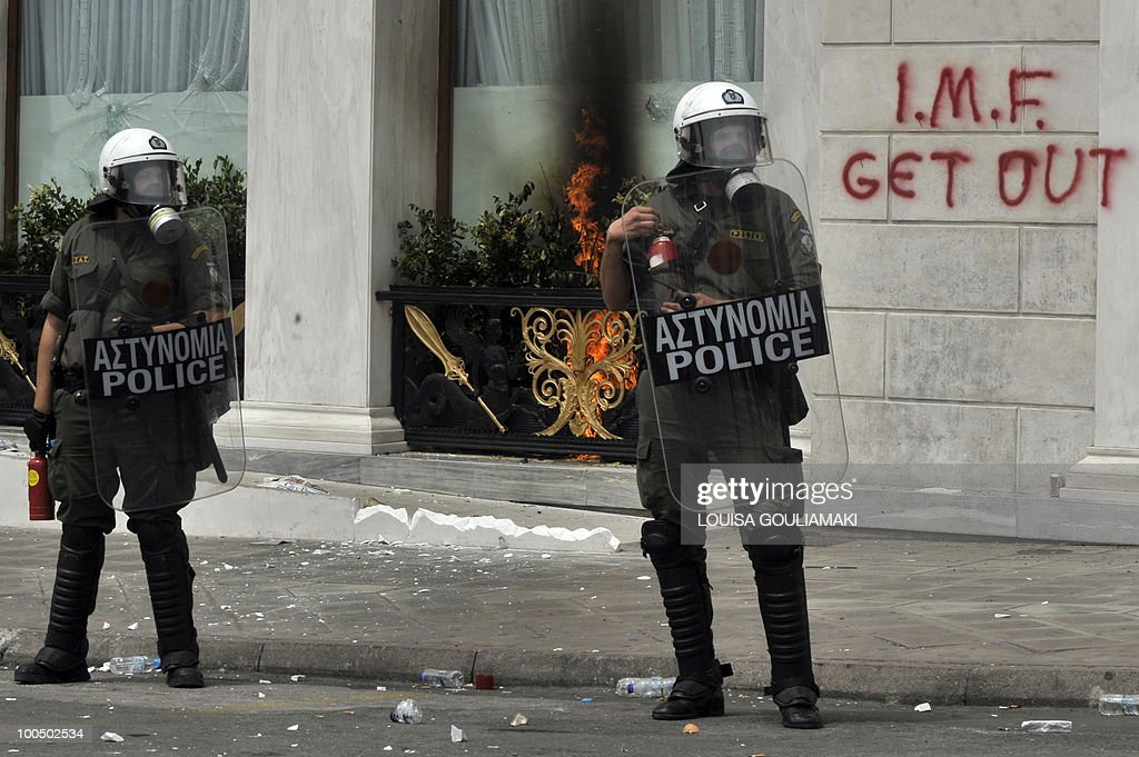 Police stands by a luxury hotel during a massive demonstration on May 5, 2010 in Athens.Three people were killed in a firebomb attack on a bank in central Athens on May 5 and around 20 people were evacuated from the building.