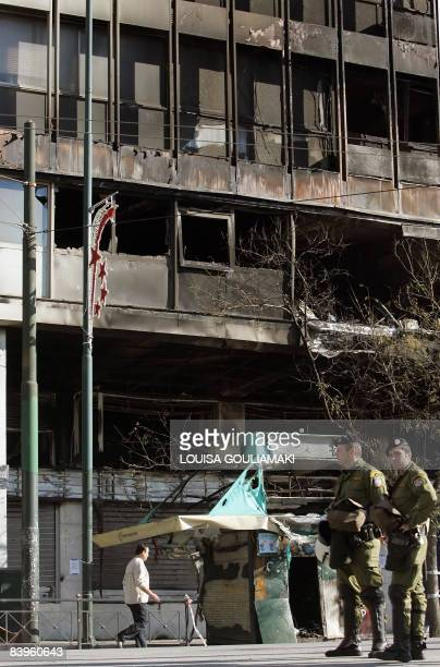 Police stands by the Emboriki bank building burned during overnight riots in Athens on December 9 2008 Authorities closed off many Athens streets...