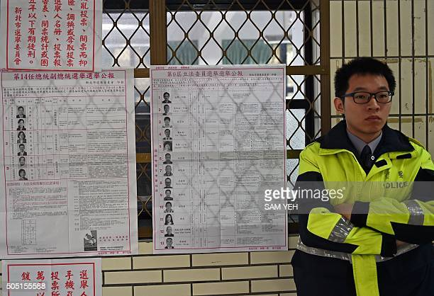 Police stands guard outside a polling station at the Xindian district in the New Taipei City on January 16, 2016. Polls opened in Taiwan with the...