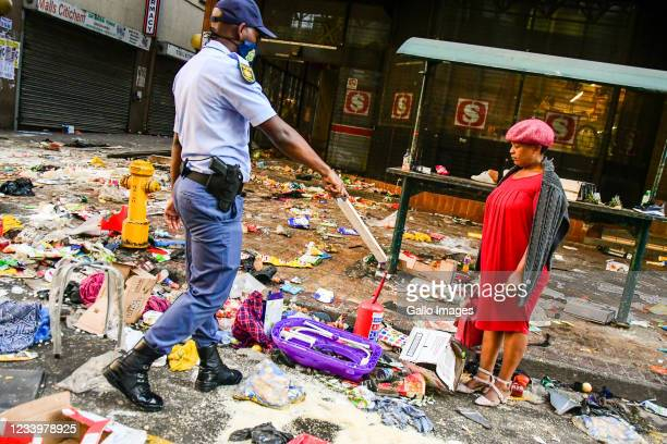 Police stop a looter outside Shoprite in Durban CBD on July 12, 2021 in Durban, South Africa. It is reported that a considerable number of shops and...