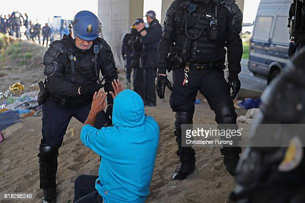 Police stop a migrant returning to the notorious Jungle camp as the authorities begin to demolish the site on October 26 2016 in Calais France...